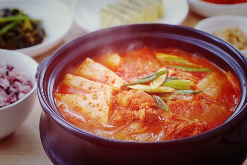 steaming iron bowl of kimchi soup