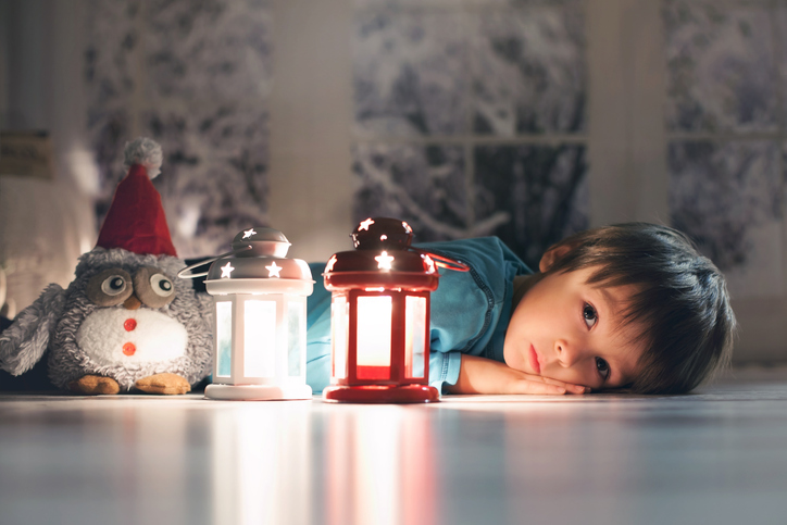 Beautiful little boy, lying down on floor, looking at candle