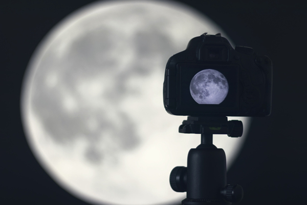 Moon photography. Camera with tripod capturing moon.